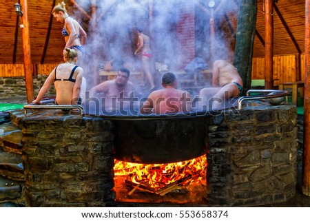 Lumshory, Ukraine - January 10, 2017: Tourists bathing in the cast iron vat with mineral water containing hydrogen sulphide. Water in cast iron vats heated to 40-45 degrees Celsius.