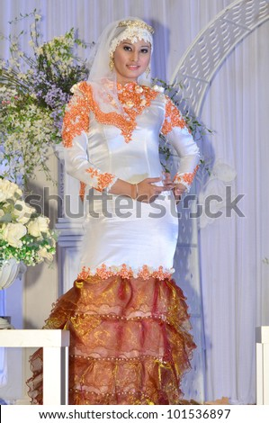 LUMUT, MALAYSIA - APR 22: A model walks the runway wearing muslimah bridal dress during Perak Bridal Carnival at Marina Island Hall on Apr 22, 2012 in Lumut Perak, Malaysia.