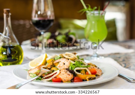 Lunch at the restaurant . Seafood salad , lemonade , glass of red wine close-up. Mussels , shrimp , salmon , squid . Delicious dinner , delicacies , exquisite selection .