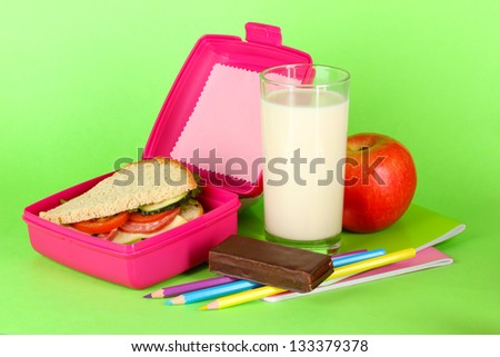 Lunch box with sandwich,apple,milk and stationery on green background - stock photo