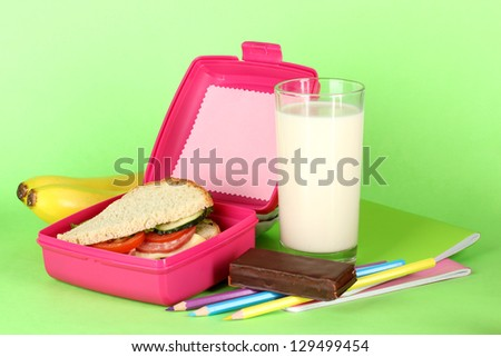 Lunch box with sandwich,bananas,milk and stationery on green background - stock photo