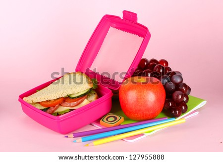 Lunch box with sandwich,fruit and stationery on pink background - stock photo
