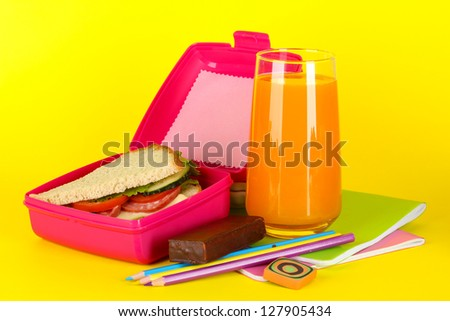 Lunch box with sandwich,juice and stationery on yellow background - stock photo