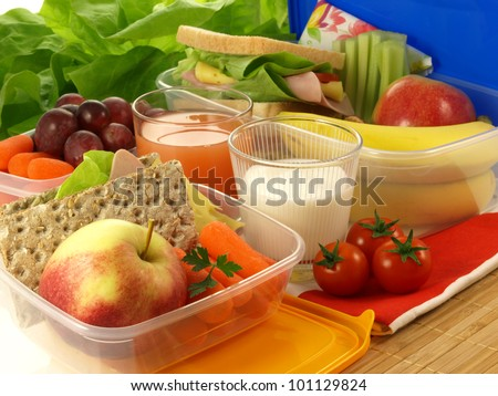 Lunch boxes filled with colorful fruits and vegetables - stock photo