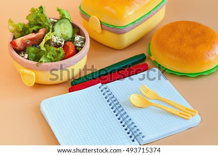 Lunch boxes for children in the form of hamburger. Fresh vegetables and fruits