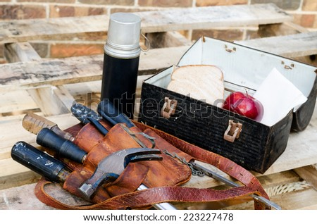 Lunch break at construction site with lunch pail, beverage container, apple, sandwich, napkin, tool belt, hammer, wrenches, screwdrivers on pallet with brick wall in background.