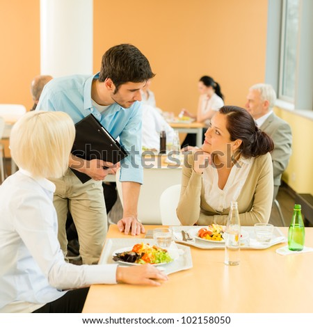 Lunch break office colleagues eat meal in cafeteria fresh salad - stock photo