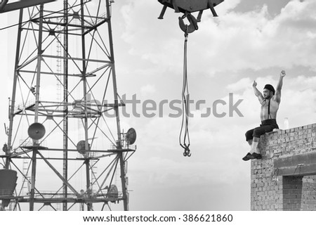 Lunch break. Sexy muscular construction worker stretching his back sitting on the top of a wall at the skyscraper monochrome shot - stock photo