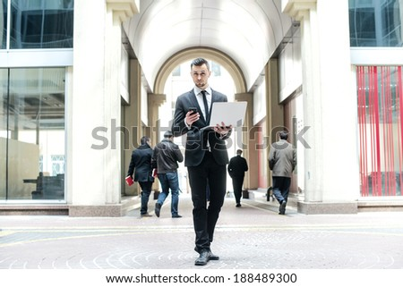 Lunch break. Young businessman receives a call from a new customer. Businessman holding a cell phone and laptop among businessmen walking around - stock photo
