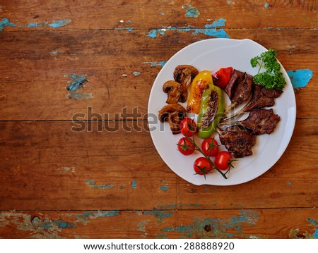 Lunch for athletes after exercise, lamb medium rare  mushrooms lightly browned, keeping all its useful properties, Lunch gourmet, fresh lamb,grilled peppers, cherry tomatoes, space for text - stock photo