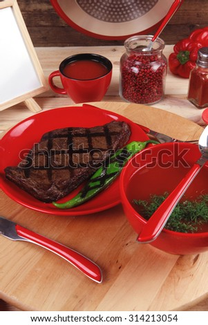 lunch fresh grilled bbq roast beef steak red plate green chili tomato soup ketchup sauce jug glass ground pepper american peppercorn modern cutlery served wooden plate table empty nameplate menu board - stock photo