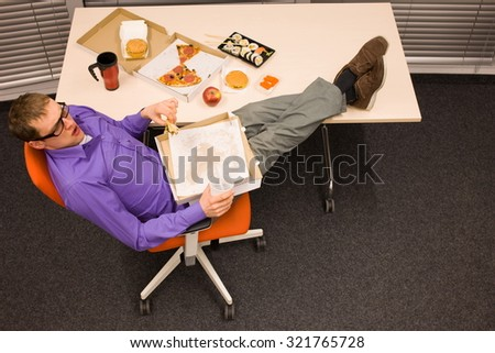 Lunch in office - man sitting with feet on the table, suffering from overeating  - stock photo