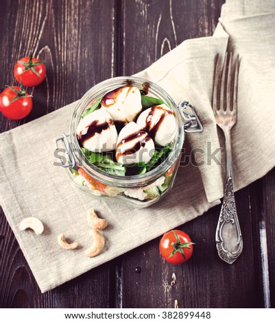lunch in the summer afternoon. Salad in mason jars with tomatoes, leaves, mozzarella on wooden table. Square image. Toned image. - stock photo