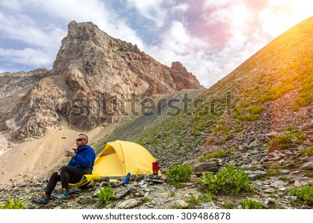 Lunch of alpine climber. Hiker sitting aside yellow camping tent and having lunch stove and cooking gear mountain landscape shining sun sunbeams on background - stock photo