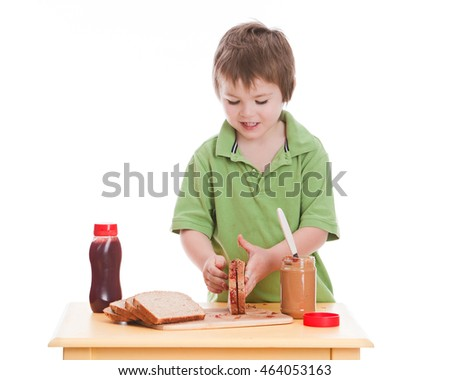 Lunch Time.  Adorable preschooler making himself a peanut butter and jelly sandwich. Isolated on white.