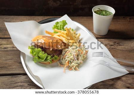 Lunch with a burger, fries, salad and sauce in a glass - stock photo
