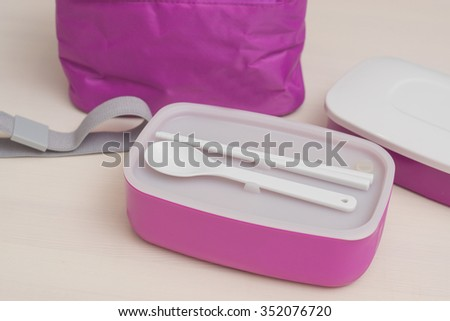 Lunchbox with sticks and spoon  - stock photo
