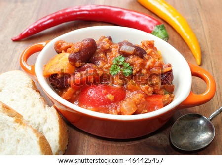 lunchtime - chili con carne in a small bowl on a wooden brown table with bread and ingredients around
