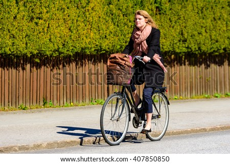 Lund, Sweden - April 11, 2016: Real life in the city. Young adult woman on a bike with her bag in the basket. Street fashion in black coat with pink scarf and dark blue trousers.