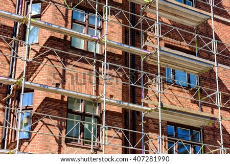 Lund, Sweden - April 11, 2016: Scaffoldings against a red brick apartment building being renovated.