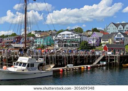 LUNENBURG, CANADA - AUG 2, 2015:  The waterfront of the UNESCO World Heritage Site town of Lunenburg, Nova Scotia, including the iconic schooner The Bluenose in dock, and location for the show Haven. - stock photo