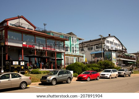 LUNENBURG, CANADA - JUL 27:  Restaurants along the waterfront draw tourists during the busy summer tourist season July 27, 2014 in the  UNESCO World Heritage Site town of Lunenburg, Nova Scotia - stock photo