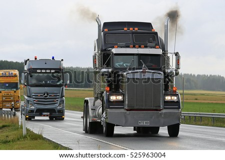 LUOPAJARVI, FINLAND - AUGUST 11, 2016: Classic Kenworth W900B semi moves along highway in rain as part of the truck convoy to the annual trucking event Power Truck Show 2016.
