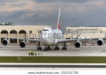 Luqa, Malta February 12, 2015: Emirates Sky Cargo Boeing 747-4HAF/ER/SCD being guided to its parking spot in apron 9 after arriving from Dubai. - stock photo