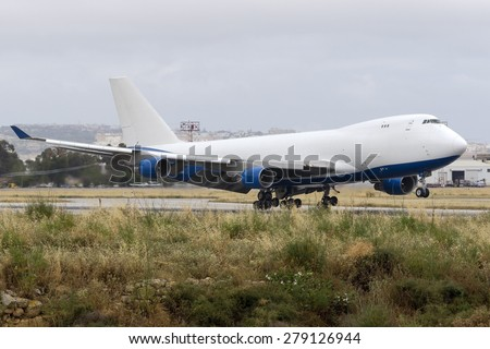 Luqa, Malta May 18, 2015: Dubai Air Wing Boeing 747-412F/SCD (A6-GGP) landing runway 13 in unusually bad weather for mid-May in Malta. - stock photo
