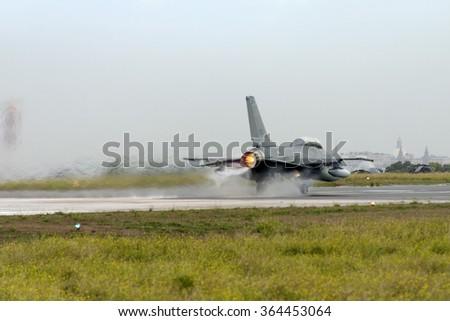 Luqa, Malta September 27, 2004: Italian Air Force General Dynamics F-16B/ADF Fighting Falcon (401) [MM7266] taking off runway 06 in afterburner. - stock photo