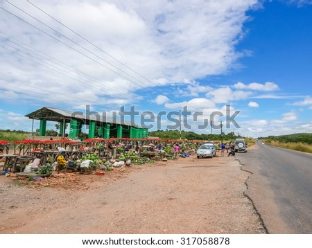 Lusaka, Zambia - April 3, 2015: People stopping at the local market place just at the road before Lusaka - stock photo