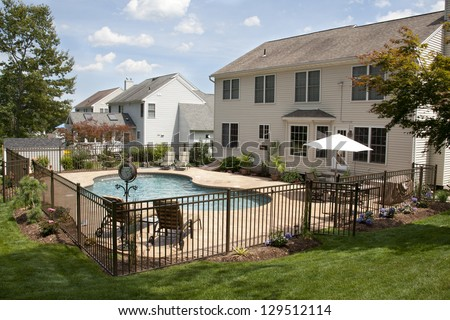 Lush backyard pool and patio behind colonial style home. - stock photo