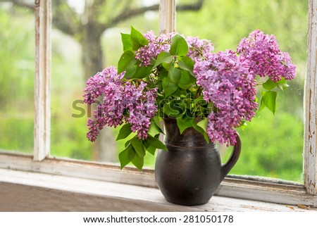 Lush bouquet of lilac in a brown clay vase on a window sill - stock photo
