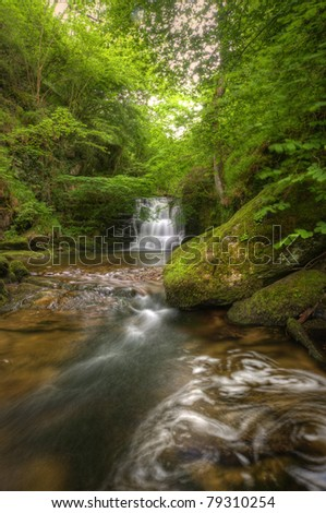 Lush green forest scene with long exposure blurred waterfall flowing through and over rocks covered in lichen and moss - stock photo