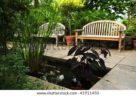 Lush green garden with stone landscaping, koi pond and benches - stock photo