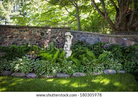 Lush green summer garden with perennial plants and statue near stone wall - stock photo
