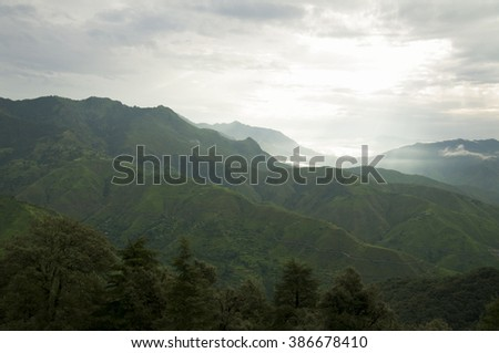 Lush green tropical mountains with a cloudy sky - stock photo
