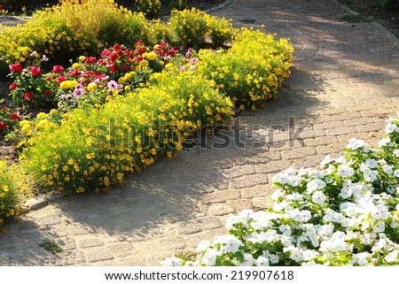Lush landscaped garden with flower bed and colorful plants - stock photo