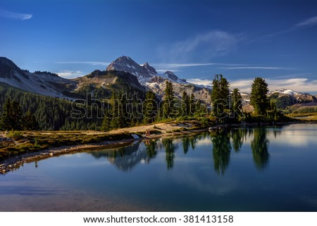 Lush trees, blue waters, snow-capped mountains, and a couple enjoying the serene atmosphere - stock photo