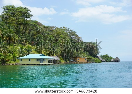 Lush vegetation on tropical coast with houses and huts over the water, viewed from the sea, Caribbean, Panama, Central America - stock photo