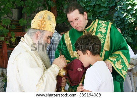 Lustica, Montenegro - August 8, 2014: Metropolitan Amfilohije, Serbian Orthodox and current Metropolitan bishop of Montenegro and the Littoral gives the Holy Communion to the faithful