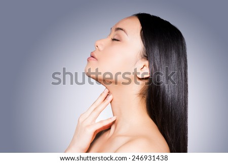 Lustrous hair and perfect skin. Side view of beautiful young and shirtless Asian woman touching her neck and keeping eyes closed while standing against grey background   - stock photo