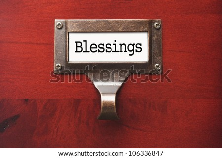 Lustrous Wooden Cabinet with Blessings File Label in Dramatic Light.