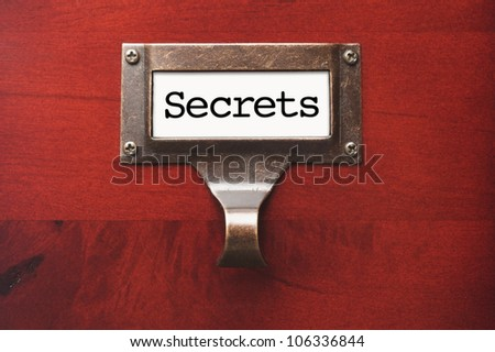Lustrous Wooden Cabinet with Secrets File Label in Dramatic Light. - stock photo