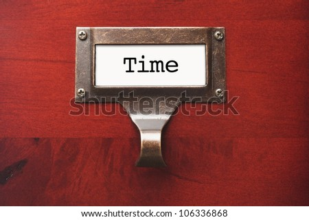 Lustrous Wooden Cabinet with Time File Label in Dramatic Light. - stock photo