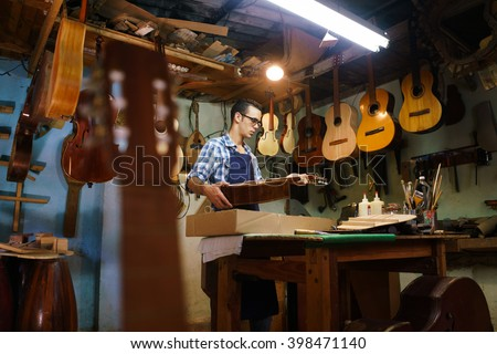 Lute maker shop and acoustic music instruments: a young adult artisan fixes an old classic guitar, then stores it in a cardboard case for his client. Wide shot - stock photo