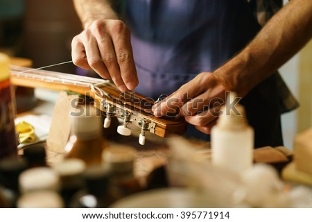 Lute maker shop and classic music instruments: young adult artisan fixing old classic guitar adding a cord and tuning the instrument. Close up of hands and palette - stock photo