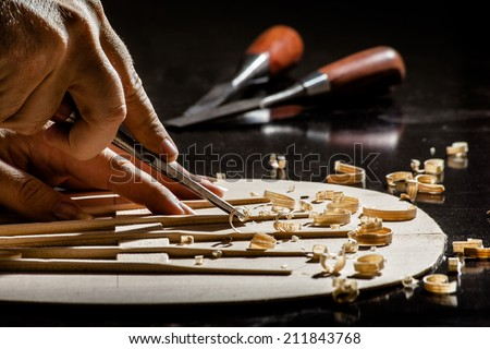Luthier making top of guitar - stock photo