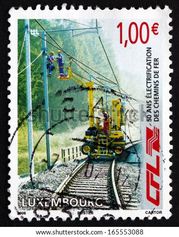 LUXEMBOURG - CIRCA 2006: a stamp printed in the Luxembourg shows Railway Workers Repairing Electrical Wires, Electrification of Railway Network, 50th Anniversary, circa 2006 - stock photo