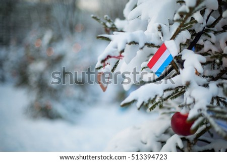 Luxembourg flag. Christmas holiday greeting card. Christmas tree covered with snow and a Luxembourg flag. Winter scene background outdoor. Xmas card design.